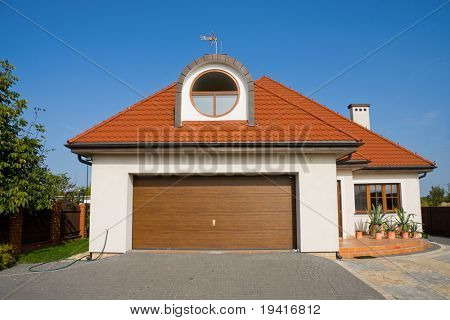 Single family white house with garage gate over blue sky