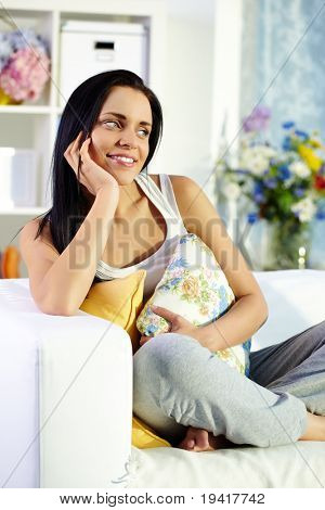 Portrait of brunette with pillows sitting on sofa at home