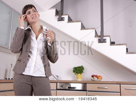 Woman suffering indoor of migraine headache pain in kitchen
