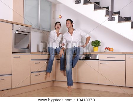 Couple having fun in the kitchen at home by throwing a apple
