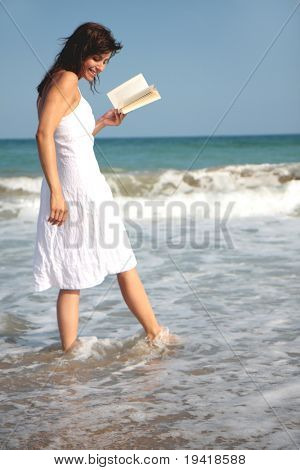 Romantic scene of a book holding woman walking the coastline