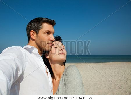 Mid adult couple on beach looking for security