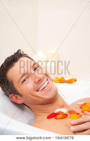 Smiling cute man having a joyful morning in bathtub