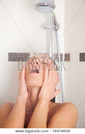 Woman having a shower under falling water