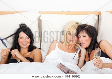 Three girls in one bed having fun in reading newspaper magazine, listening music, singing and combing hairs while celebrating bachelorette party at home living in a flat share community