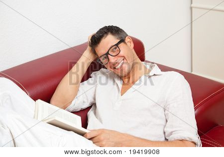 Cute smiling man reading and learning book lessons sitting on couch