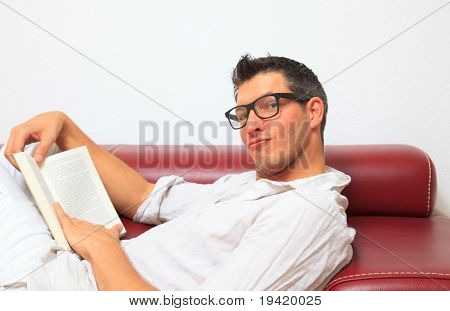Man enjoining freeteim with book at home