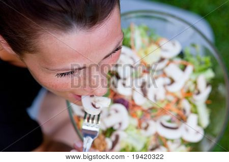 Garden sitting healthy woman eating salad holding big bowl . photo from above