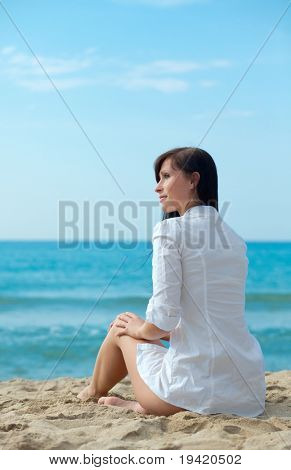 Relaxing white dressed sitting brunette woman on the blue ocean with blue sky alone feeling carefree