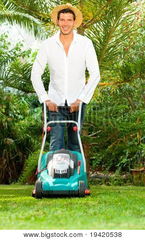 Man cutting green grass at home in tropical garden