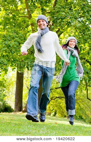 Active running couple through colorful parc with warm clothes and scarf
