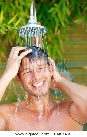 Showering happy healthy splash man in tropical vacation wellbeing wellness spa  resort hotel