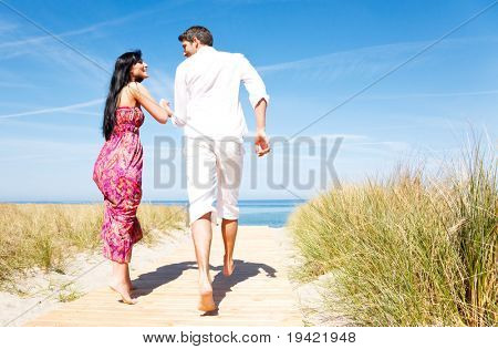 Romantic couple running to holiday vacation in summertime with blue sky beyond holding eachother
