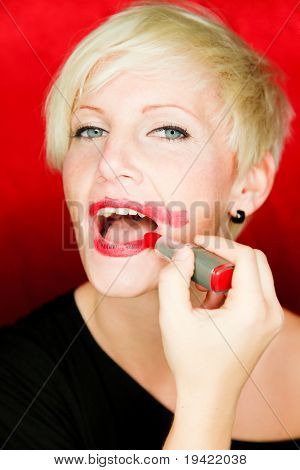 Pretty blonde woman putting on red lipstick looking in mirror hurry up because of being late