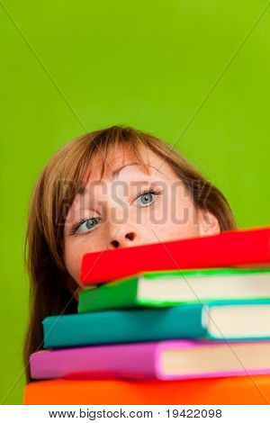 Female face behind a booktower looking