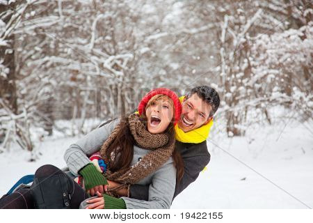 Playful winter couple sledding on sled in park