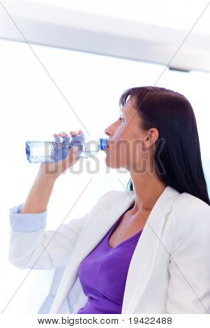 Window sitting waiting water drinking business woman