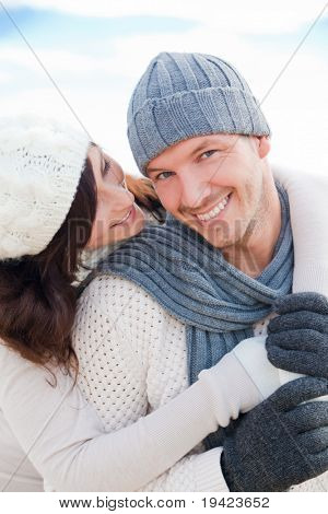 happy pair of male and female embracing and having fun wearing warm clothes outside on coast behind blue sky