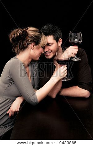 Wine drinking young couple flirting