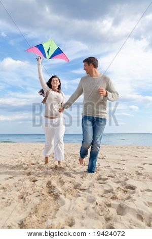 Happy outdoor couple embracing and running on beach  a kite fly