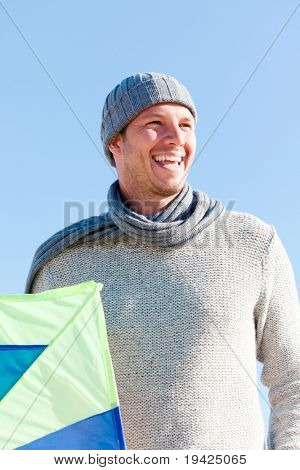 Smiling happy healthy man walking on beach with kite in winter autumn spring time