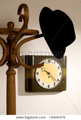 hat on a hanger with a clock in the background