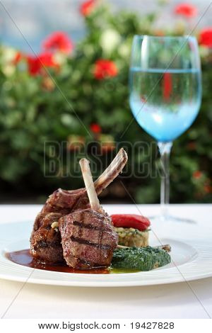 lamb chops served with risotto on a plate with glass of water