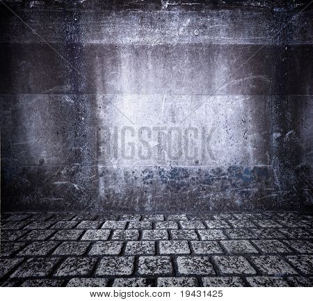 Grungy wall and cobble stone floor.