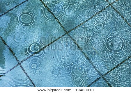 rain drops on a puddle surface, circular water ripples.