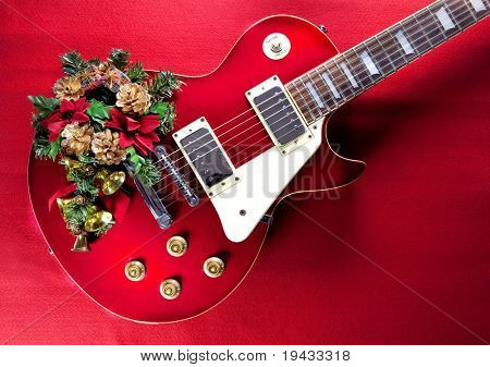 Red guitar with christmas ornaments. Image for christmas / holiday season music event.