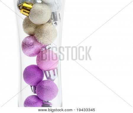 Christmas ornaments in a Champagne glass. Christmas ball ornaments stacked in a champagne glass isolated on white. Concept image for holiday season events and parties.
