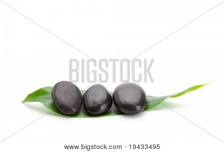 Three zen stones on a bamboo green leaf , isolated on white.
