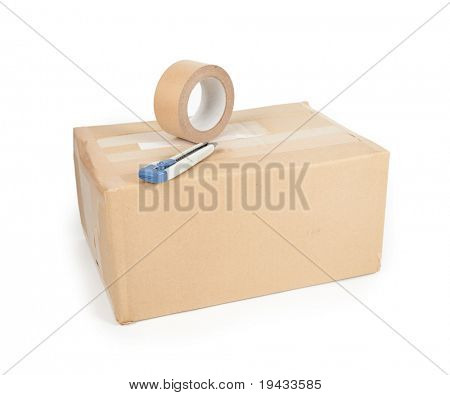 A reused card board box with packaging tape and a box cutter on top.