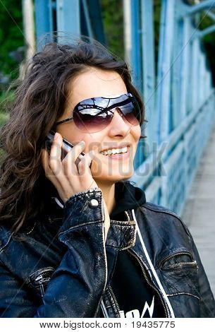 beautiful girl in leather jacket talking on the phone