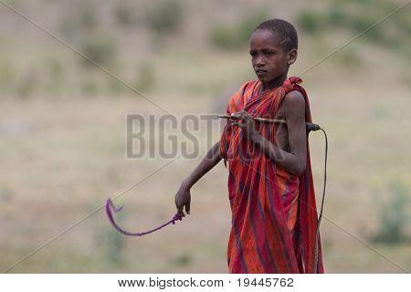 SERENGETI, TANZANIA - JUNE 6: Unidentified Masai People walk in the Africa bush to protect cattle on June 6, 2010 in the Serengeti, Tanzania.