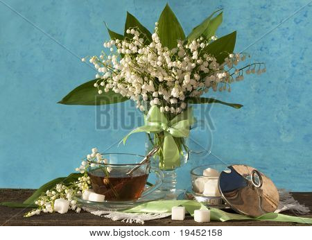 with lilies and a cup of tea and spring white and pink flowers