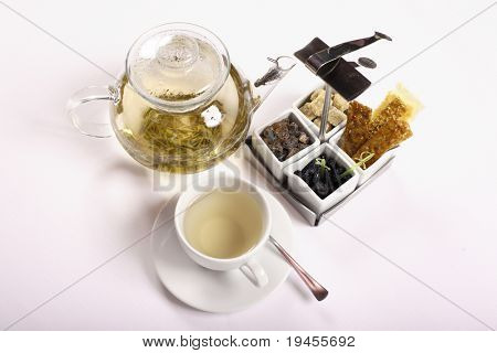 Transparent teapot with green tea, cup, saucer, sugar and other stuff on white cloth (high key)