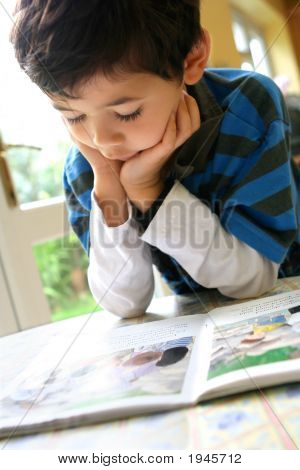 Young Boy Enjoying His Reading Book Chin Propped On Palm
