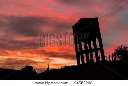 Old water tower leaning over on a hill side with a fire like sunset sky.