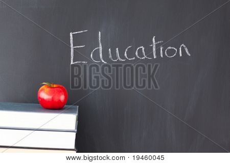 "Stack of books with a red apple and a blackboard with ""education"" written on it"