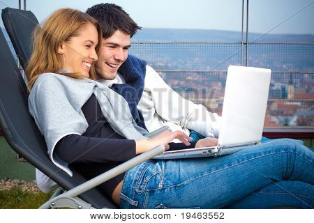 Happy Young couple surfing the internet outside