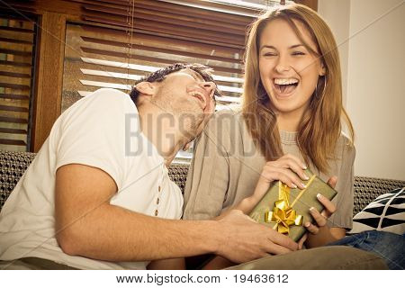 Happy young couple having fun on the sofa, girl recieves present