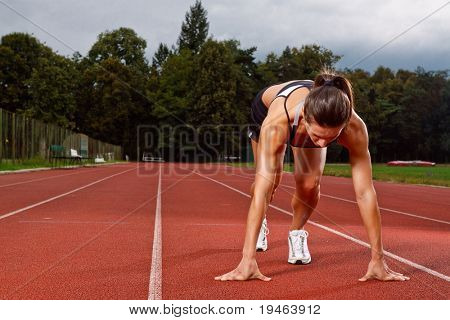 Athletic woman in start position on track