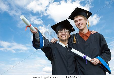 two excited graduate students in gown with risen hands holding diploma over blue sky