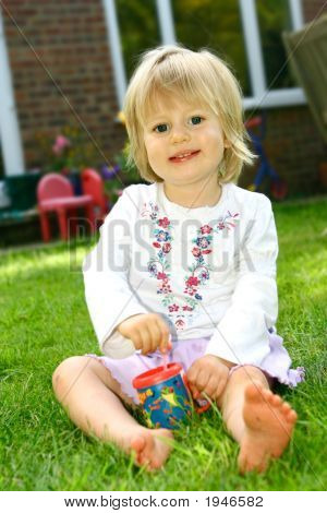 Girl Toddler With Bubble Mixture Outdoor In Summer