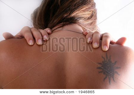 Woman with shoulder tattoo rubs her muscles