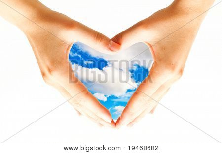 Heart formed by female hand with sky inside