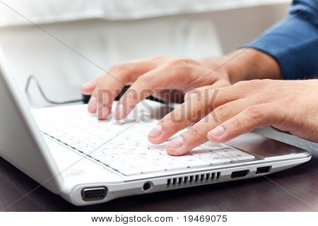 Typing on a white laptot
