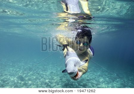Cute boy playing with toy shark underwater