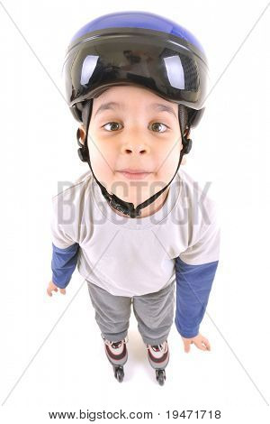 White background studio image of a cute skater boy ready to ride on roller skates looking up.